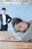 Young businesswoman sleeping during meeting, disappointed Boss looking at her Royalty Free Stock Images