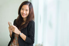 Young businesswoman smile, standing while carrying her cellphone Stock Images
