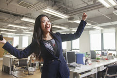 Young businesswoman smiling with arms raised in the office Stock Image