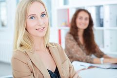 Young businesswoman, with smiling female colleague on the background. Portrait of young businesswoman, with smiling female colleague on the background royalty free stock images