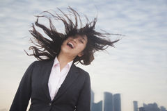 Young businesswoman smiling with hair blowing, cityscape in the background Royalty Free Stock Images