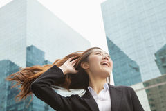 Young Businesswoman smiling with hair blowing in the wind, outdoors, Beijing Stock Images