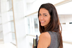 Young businesswoman smiling holding files. Young businesswoman in modern building holding files Stock Photo