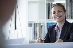 Young businesswoman smiling in the office during a business meeting Royalty Free Stock Photos