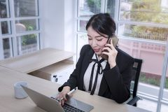 Young businesswoman smiling sign a document and talking with phone at office.Woman hands typing on computer keyboard .Copy space. stock images