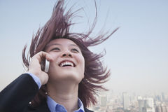Young businesswoman smiling using her cell phone with hair blowing Royalty Free Stock Images