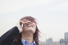 Young businesswoman smiling using her cell phone with hair blowing, city in the background Stock Image