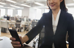 Young Businesswoman smiling and using her phone at the office Stock Photo