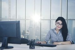 Young businesswoman smiling by the window stock images