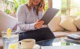 Businesswoman speaking on phone and looking at tablet Stock Photos