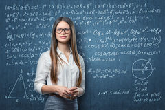 Young businesswoman standing on the background of blackboard with mathematical formulas Royalty Free Stock Photography
