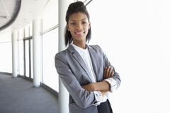 Young Businesswoman Standing In Corridor Of Modern Office Buildi Stock Photo