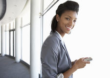 Young Businesswoman Standing In Corridor Of Modern Office Buildi Stock Images