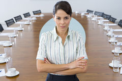 Young businesswoman standing at head of conference table, arms crossed, portrait, Stock Images