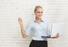 Young businesswoman standing and holding laptop while pointing a Stock Image
