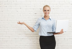 Young businesswoman standing and holding laptop while presenting Stock Photos