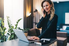 Young businesswoman standing indoor, working on computer, while talking on cell phone. Girl entrepreneur works at home. Young smiling businesswoman in black Stock Photos