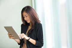 Young businesswoman standing while look at a tablet pc Stock Photo