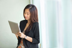 Young businesswoman standing while look at a tablet pc Stock Image
