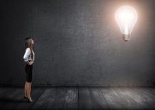 Young businesswoman standing and looking at big glowing light bulb in front of her Royalty Free Stock Photo