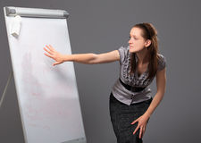 Young businesswoman standing next to flip board and pointing hand Royalty Free Stock Photography