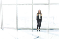 Young Businesswoman standing in office against panoramic windows Royalty Free Stock Photos