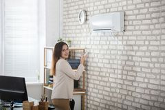 Businesswoman Using Remote Control Of Air Conditioner. Young Businesswoman Standing In Office Using Remote Control Of Air Conditioner Stock Photo