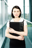 Young businesswoman standing on office walkway holding folder of papers Royalty Free Stock Image