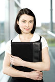 Young businesswoman standing on office walkway holding folder of papers Stock Photography