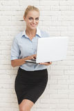 Young businesswoman standing and smiling while holding laptop Royalty Free Stock Photography