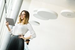 Young businesswoman standing wirth tablet in the office by windo. Portrait of young businesswoman standing wirth tablet in the office by window Royalty Free Stock Photo