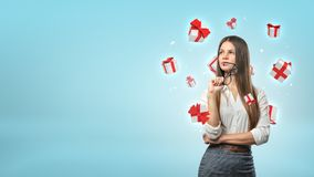 A young businesswoman stands thinking while small white and red gift boxes fly around her head. Ideas for presents. Choose client bonuses. Free gifts selection Royalty Free Stock Image