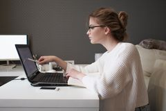 Young businesswoman stares at the screen. Beautiful girl with glasses working at home with laptop Royalty Free Stock Photo