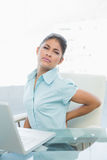 Young businesswoman suffering from back ache in office Stock Image