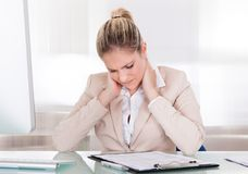 Young businesswoman suffering from neck pain at office stock photos