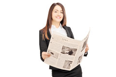 Young businesswoman in suit leaning on a wall and holding a news Royalty Free Stock Image