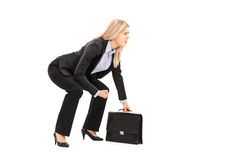 Young businesswoman in sumo wrestling stance holding suitcase Royalty Free Stock Image