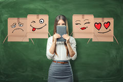 Young businesswoman surrounded by flying cardboard boxes with different faces drown on them. Young businesswoman surrounded by flying cardboard boxes with Royalty Free Stock Photos