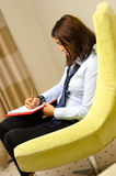 Young businesswoman taking notes. And sitting on an armchiar Royalty Free Stock Image