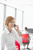 Young businesswoman talking on cell phone with colleagues in background at office Royalty Free Stock Images
