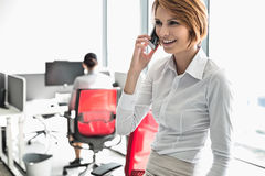 Young businesswoman talking on cell phone with colleagues in background at office Stock Photos
