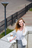 Young businesswoman talking on cellphone while walking outdoor Royalty Free Stock Photography