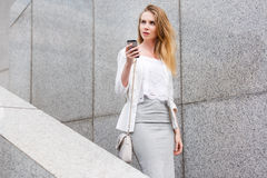 Young businesswoman talking on cellphone while walking outdoor Stock Photos