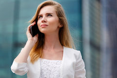 Young businesswoman talking on cellphone while walking outdoor Stock Images