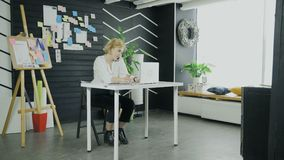 Young businesswoman is talking on her smartphone while typing on notebook stock video footage