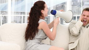 Young businesswoman talking through a megaphone Stock Photo
