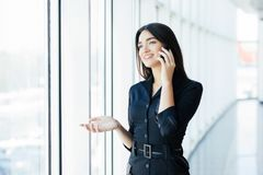 Young businesswoman talking on mobile phone while standing by window in office. Beautiful young female model in bright office. stock photo