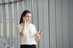 Young businesswoman talking on mobile phone while standing by window in office. Beautiful young female model in office. Young businesswoman talking on mobile royalty free stock photography