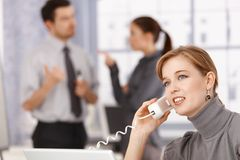 Young businesswoman talking on phone in office. Colleagues chatting in background Royalty Free Stock Photos