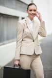 Young businesswoman talking on phone. Outside in the city Stock Photo